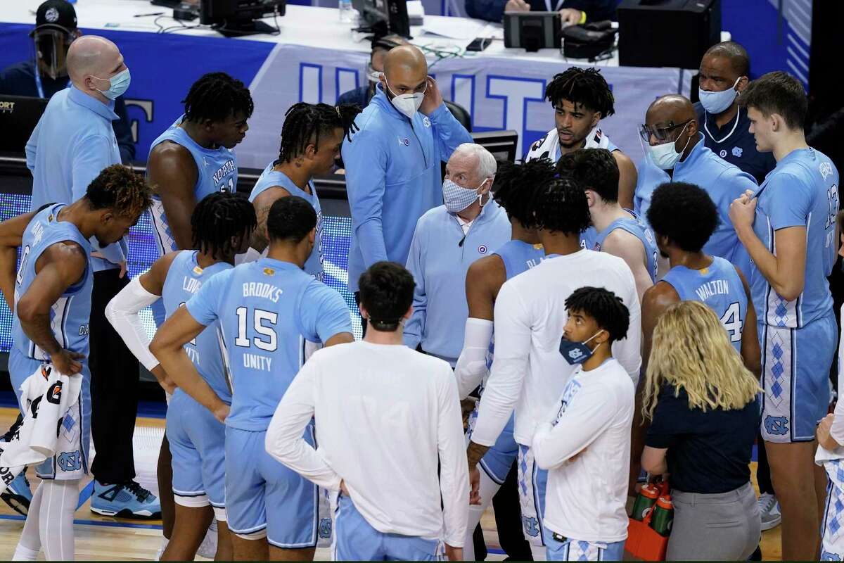 North Carolina head coach Roy Williams, center, talks with his team during the first half of an NCAA college basketball game in the quarterfinal round of the Atlantic Coast Conference tournament in Greensboro, N.C., Thursday, March 11, 2021.