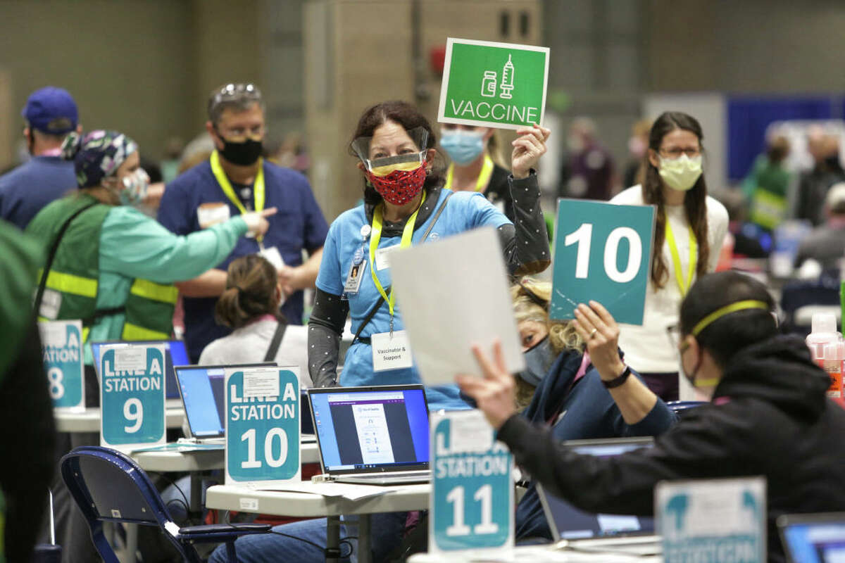 Staff and volunteers work vaccination stations during opening day of the Community Vaccination Site, a collaboration between the City of Seattle, First & Goal Inc., and Swedish Health Services, at the Lumen Field Event Center in Seattle, Washington, on March 13, 2021.