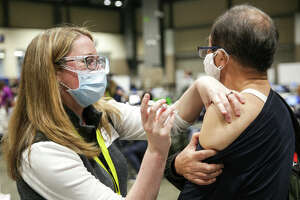 Nurse Jaime Navetta gives the Pfizer Covid-19 vaccine to Tianji Yu during opening day of the Community Vaccination Site, a collaboration between the City of Seattle, First & Goal Inc., and Swedish Health Services at the Lumen Field Event Center in Seattle, Washington on March 13, 2021.