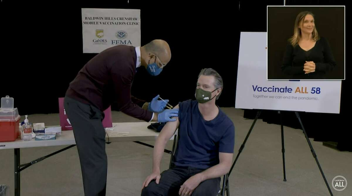 Gov. Gavin Newsom is administered the coronavirus vaccine by Mark Ghaly, California's health and human services secretary, in Baldwin Hills (Los Angeles County).