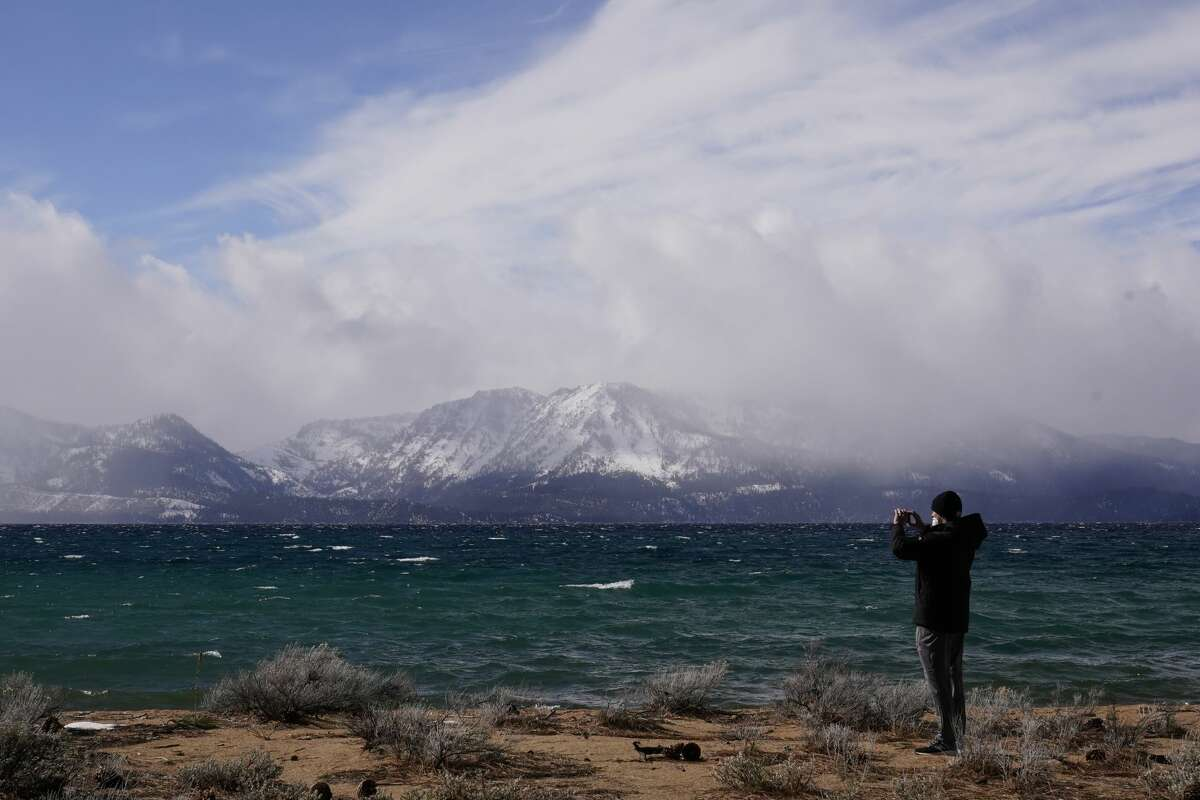 A person takes in the view of Lake Tahoe along the shore of the Edgewood Tahoe Resort in February. As Tahoe heads into its traditionally slower off-season during the spring, winter's crowds are sticking around.