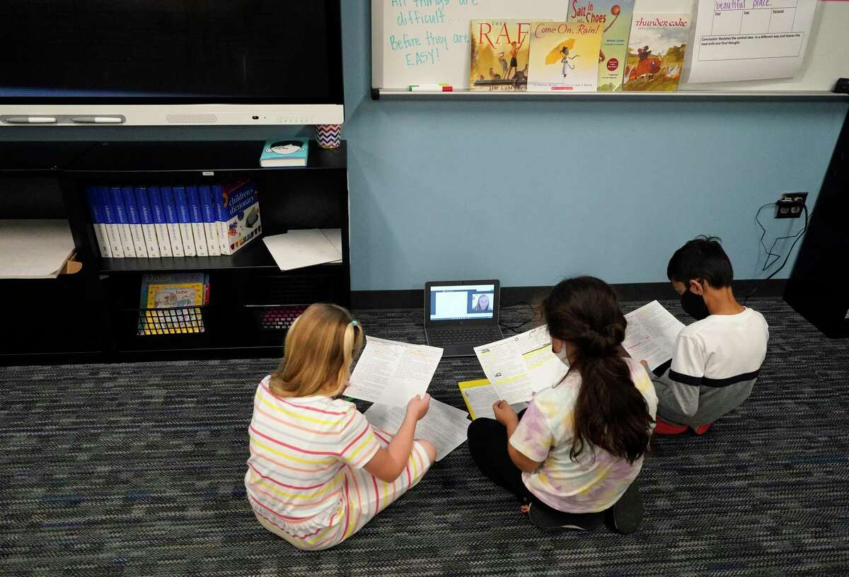 Third graders Kelli Blair, 9, left, Jennifer Rosa, 8, and Niam Patel, 8, right, participate in a virtual session with A&M senior Grace Neal during their class at Grand Oaks Elementary School, 20241 Cypress Rosehill Rd., Thursday, March 25, 2021 in Tomball. Seniors at Texas A&M's College of Education are undertaking their student teaching by streaming into Tomball ISD's classrooms this year.