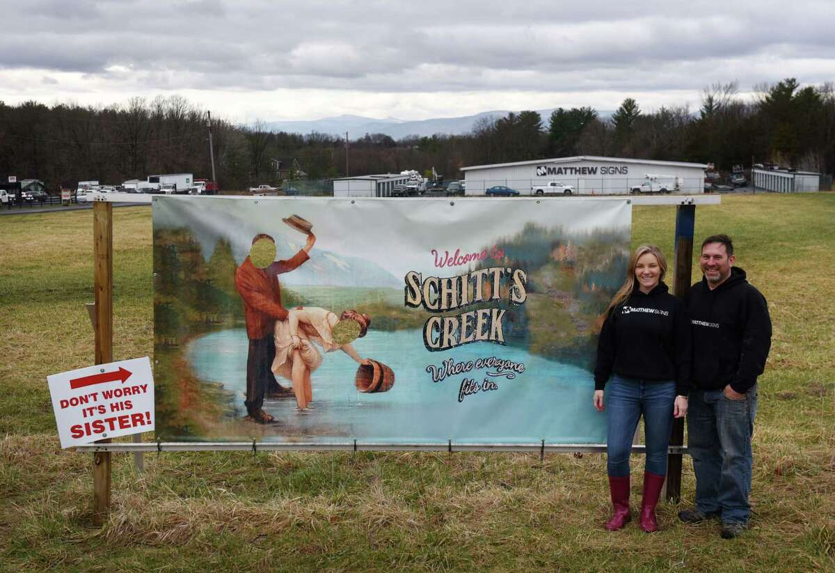 """Mathew Kusewich and Misty Brew-Kusewich of Matthew Signs pose by the likeness of a welcome sign used in the sitcom """"Schitt's Creek"""" which they put up as a novelty in front of their business on Thursday, April 1, 2021, on Route 9 in Stockport, N.Y. The sign sent one driver to the state Department of Transportation and the town, demanding its removal. (Will Waldron/Times Union)"""