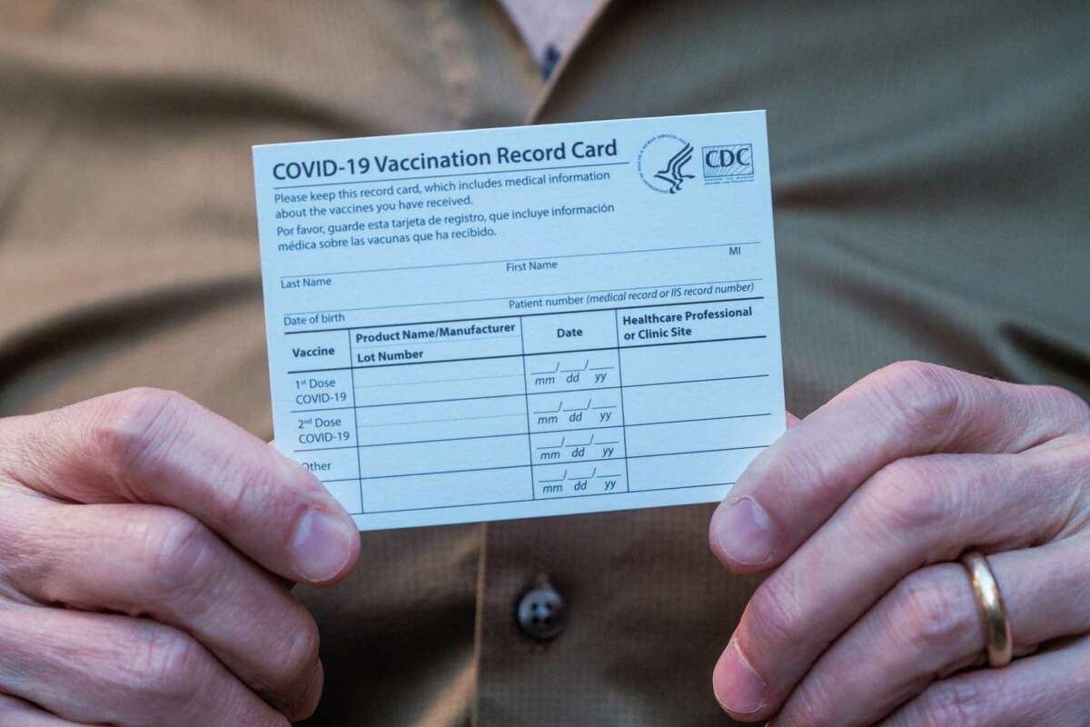 Dr. Stephen Hall, director of psychiatry at the San Francisco Campus for Jewish Living, holds an all-important vaccination card after receiving the coronavirus vaccine in December.