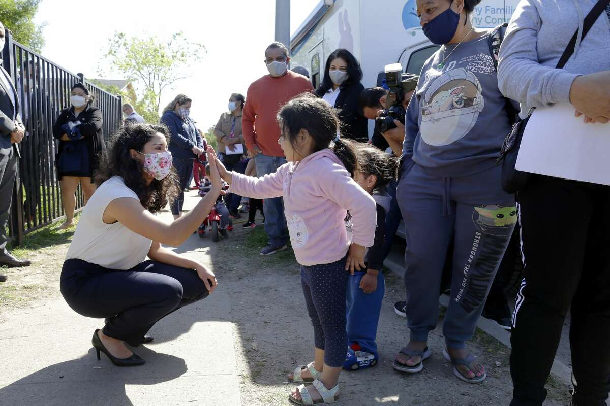 Harris Co. Judge Lina Hidalgo, left, crouches to high five Amanda Isabell, age four, as her grandmother Maria Benitez, right, looks on as Hildalgo talks with area residents in line for the vaccine at Pitner Pocket Park Thursday, Apr. 1, 2021 in Houston, TX.