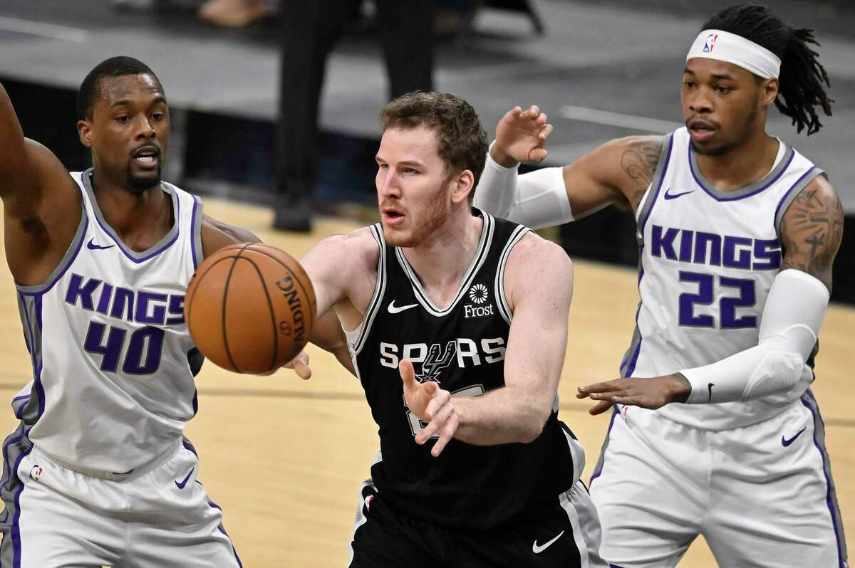 San Antonio Spurs' Jakob Poeltl, center, passes the ball as he is defended by Sacramento Kings' Harrison Barnes (40) and Richaun Holmes during the first half of an NBA basketball game Wednesday, March 31, 2021, in San Antonio. (AP Photo/Darren Abate)