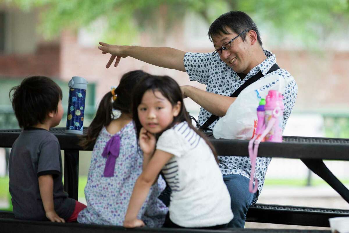 Hideaki Takahashi plays around with his children and a young neighbor during a visit to the Old Braeswood Park in May of 2019, while the neighborhood was engaging in a successful campaign to remove racist language from its deed restrictions. The process is difficult and requires significant resources; a new bill would make it simpler for neighborhoods to remove such language.