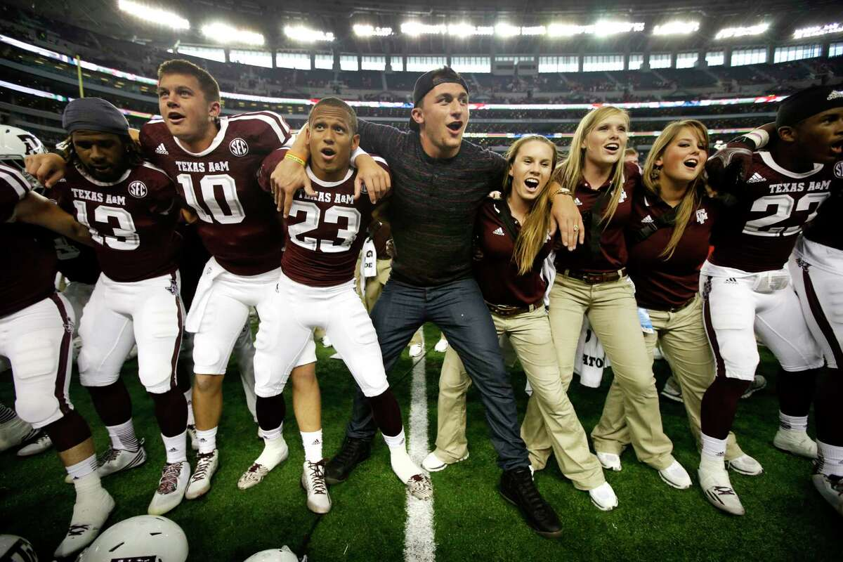 Cleveland Browns quarterback and former Texas A&M quarterback Johnny Manziel, center, joins the team and staff as they sing the Aggie War Hymn after the Aggies 35-28 overtime win against Arkansas in an NCAA college football game, Saturday, Sept. 27, 2014, in Arlington, Texas.