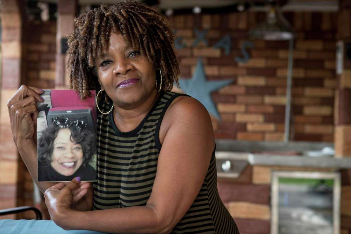 Janice Carter poses for a portrait holding a photo of her late sister, Deborah Kiel, on her back porch Wednesday, March 31, 2021 in Houston. Kiel died after losing power during the February winter storm.