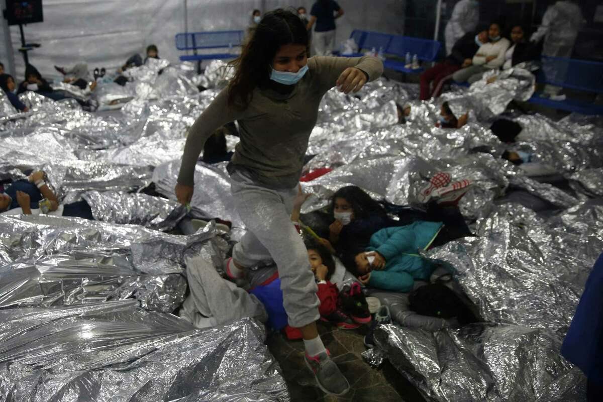 A young female minor walks over others as they lie inside a pod for females at the Donna Department of Homeland Security holding facility, the main detention center for unaccompanied children in the Rio Grande Valley run by the US Customs and Border Protection, (CBP), in Donna, Texas on March 30, 2021.