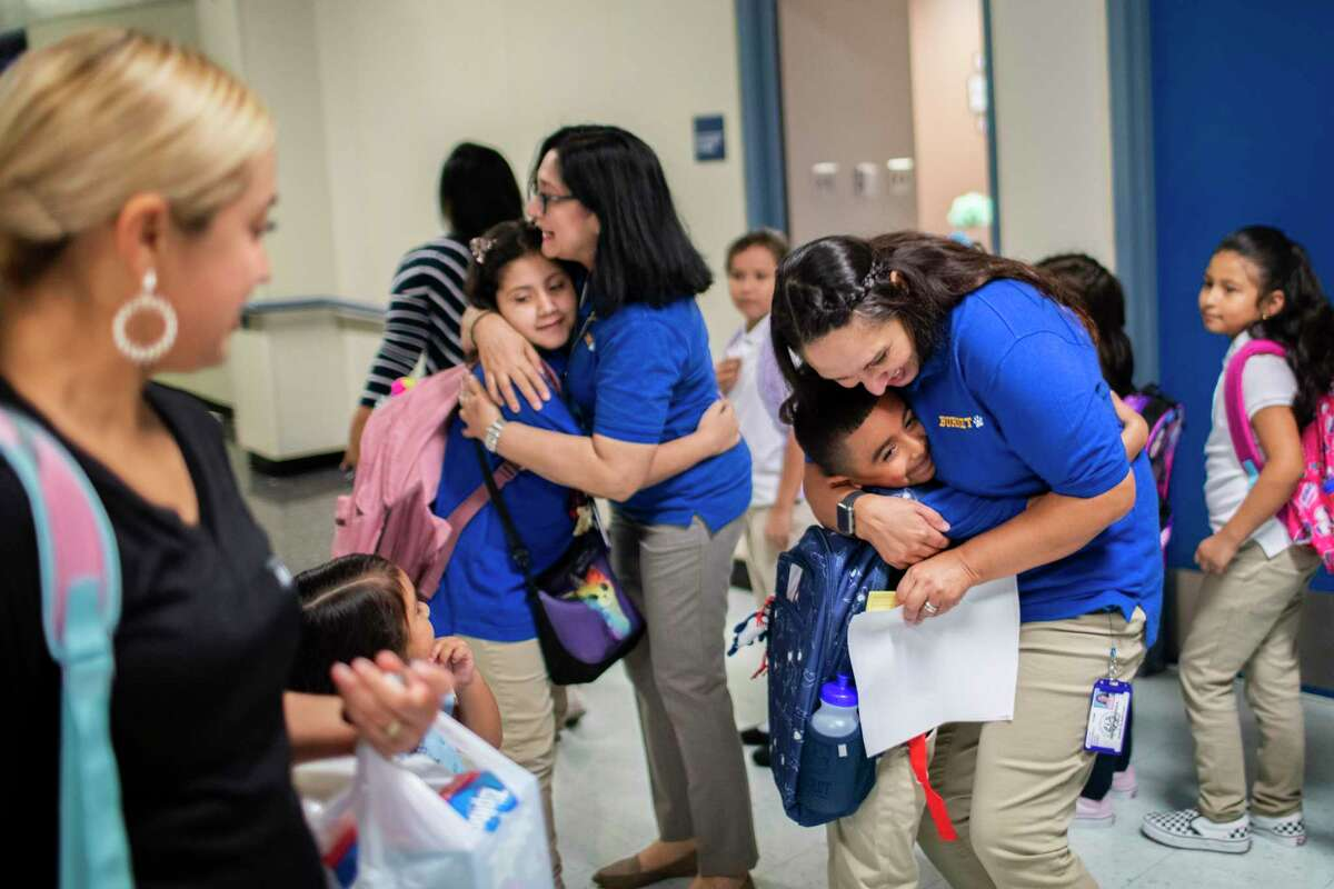 Teachers at Houston ISD's Burnet Elementary School, pictured in 2019, hug students arriving for the first day of classes to start the new academic year. HISD will continue to begin the school year in late August after a district committee last week rejected a plan that would, in part, allow the district to move up its start date.