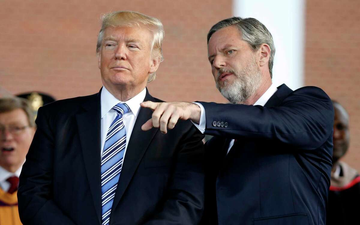 FILE - In this May 13, 2017 file photo, President Donald Trump stands with Liberty University President Jerry Falwell Jr. in Lynchburg, Va. On Tuesday, Aug. 25, 2020, Falwell said that he has submitted his resignation as head of evangelical Liberty University. (AP Photo/Steve Helber)