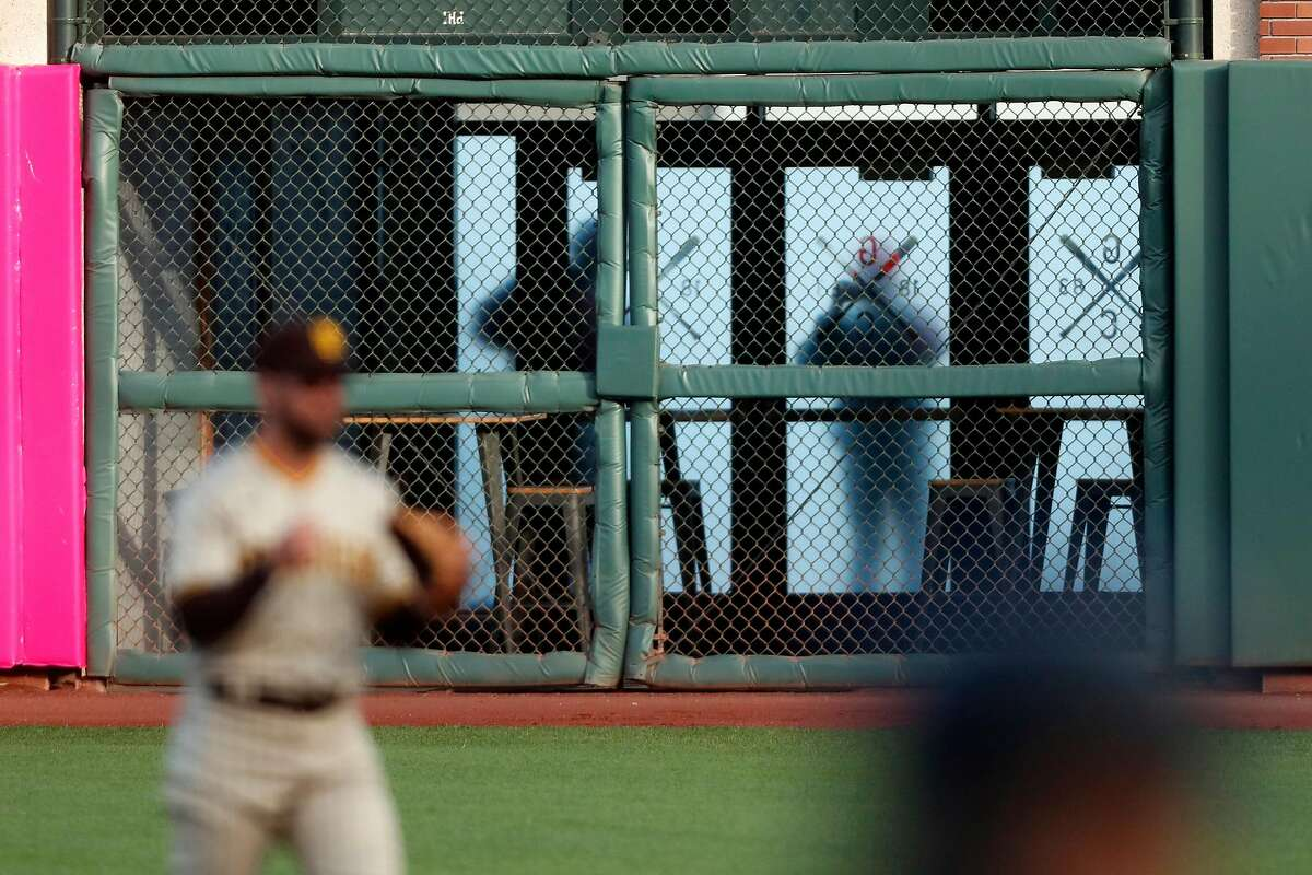 Fans peek in through glass doors behind right field wall as San Francisco Giants play San Diego Padres during MLB game at Oracle Park in San Francisco, Calif., on Wednesday, July 29, 2020.