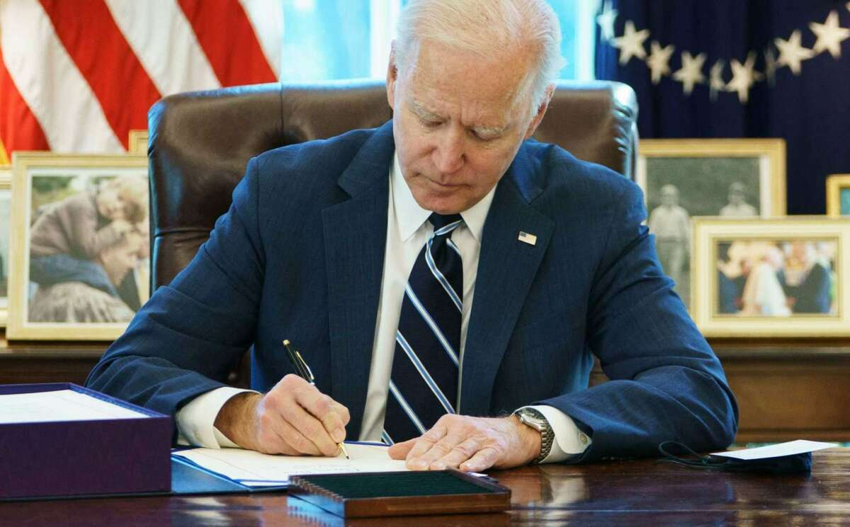 President Joe Biden signs the $1.9 trillion American Rescue Plan on March 11, 2021, in the Oval Office of the White House in Washington, D.C.