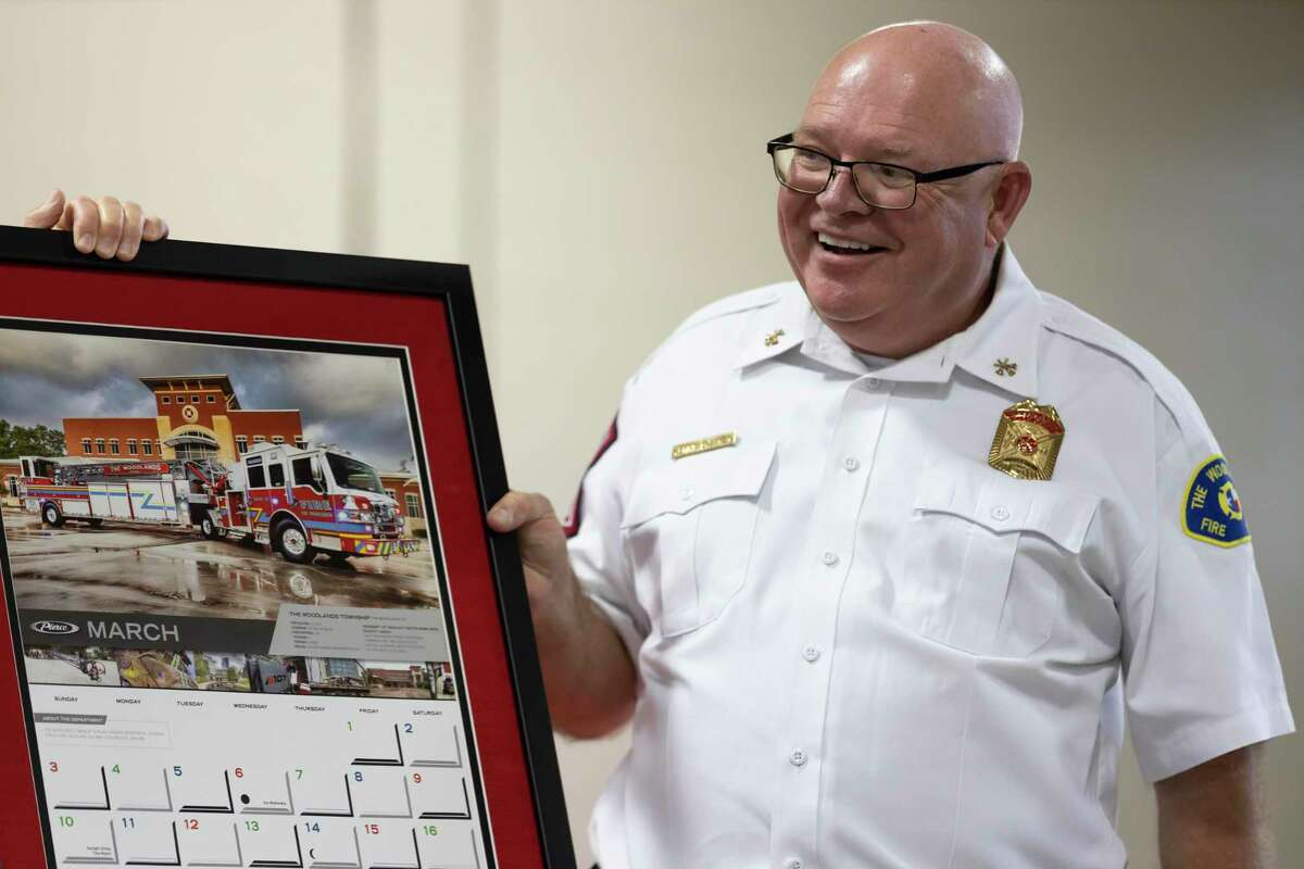 Deputy Fire Chief Jerry Bittner reacts after receiving a frame calendar during a retirement party in his honor at the Woodlands Fire Department Administration and Station 1, Wednesday, March 31, 2021, in The Woodlands. Bittner served with the fire department for over 40 years before retiring.