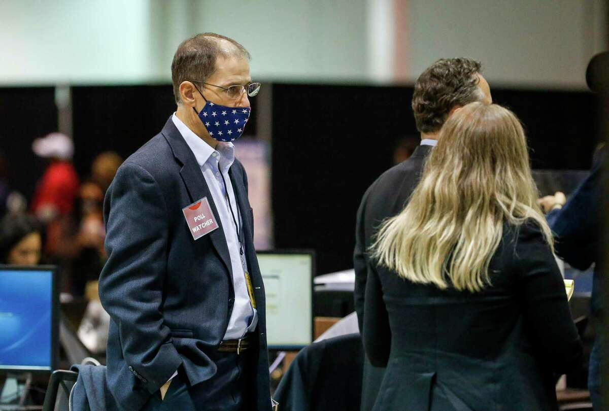 A poll watcher looks on as election workers work before the release of early-voting returns in Harris County on Tuesday, Nov. 3, 2020, at NRG Arena in Houston.