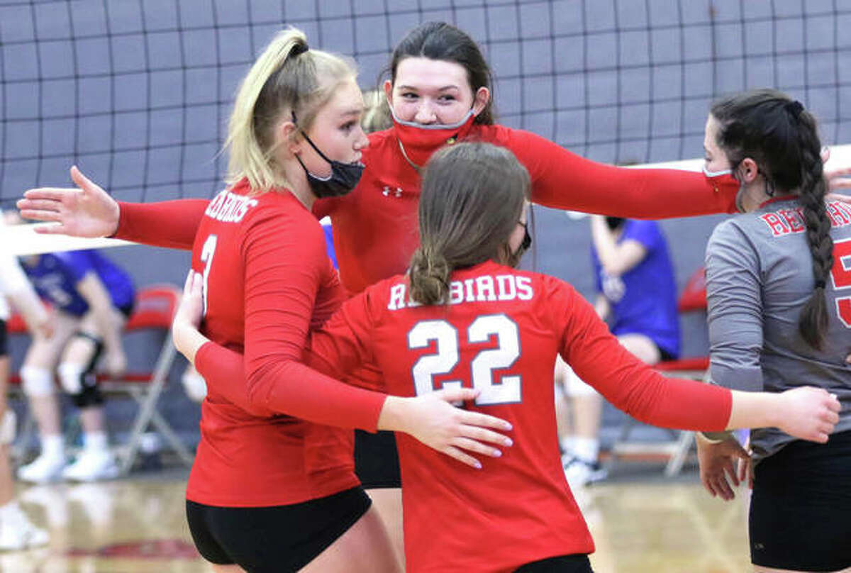 Alton's Brooke Wolff (back) celebrates a win over Marquette Catholic with teammates Taylor Freer (left), Payton Olney (22) and Audrey Evola on Saturday at Alton High in Godfrey.
