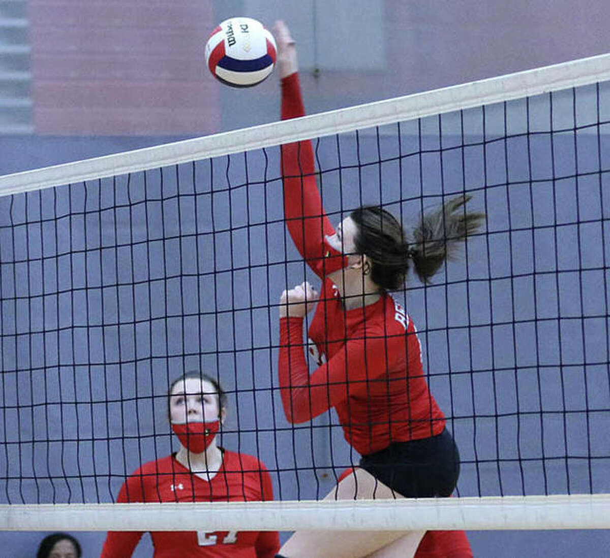 Alton senior middle hitter Brooke Wolff attacks for one of her xx kills in Saturday's match vs. Marquette Catholic at Alton High in Godfrey.