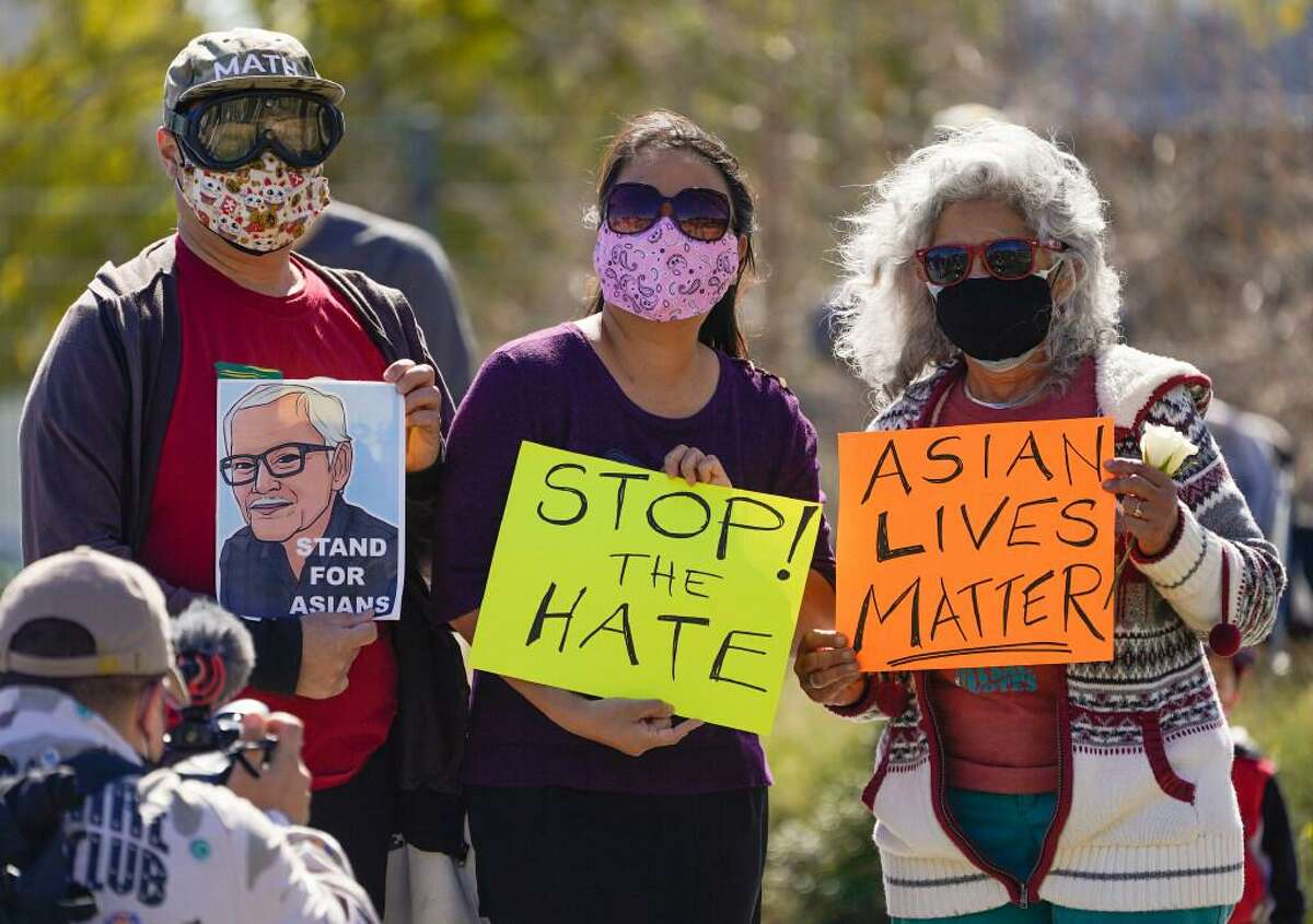 A man holds a portrait of late Vichar Ratanapakdee, left, a 84-year-old immigrant from Thailand, who was violently shoved to the ground in a deadly attack in San Francisco, during a community rally to raise awareness of anti-Asian violence and racist attitudes, in response to the string of violent racist attacks against Asians during the pandemic, held at Los Angeles Historic Park near the Chinatown district in Los Angeles, Saturday, Feb. 20, 2021.