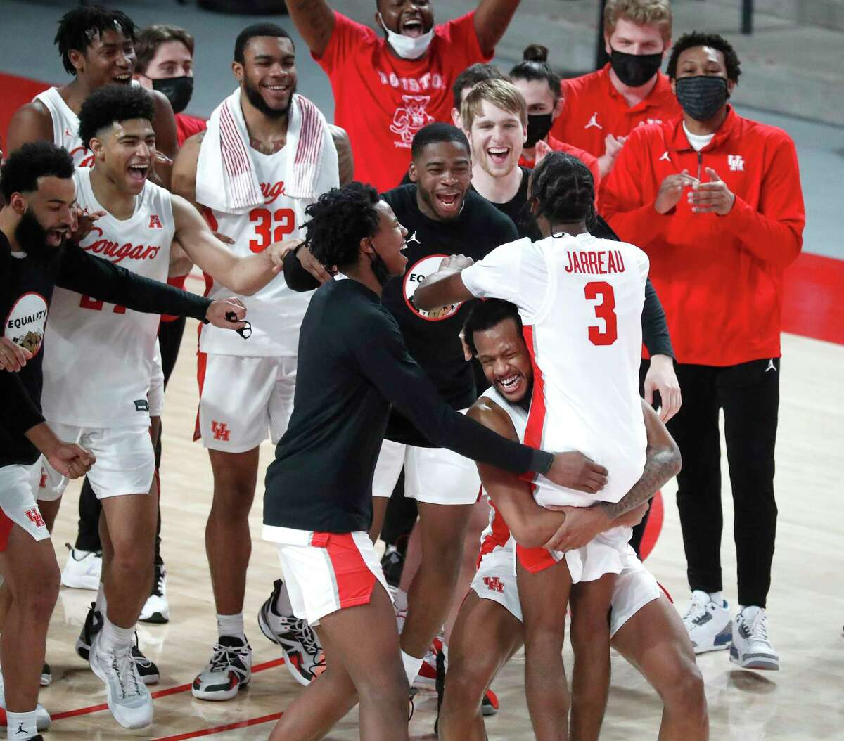 Houston Cougars guard DeJon Jarreau (3) hugged by Justin Gorham (4) after he addressed the fans after the Cougars 64-67 win over Memphis Tigers an NCAA Men's basketball game at the Fertitta Center, Sunday, March 7, 2021, in Houston.