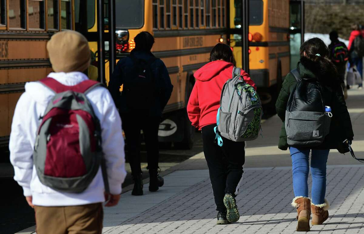Students dismiss from Brien McMahon High School Friday, February 26, 2021, in Norwalk, Conn.