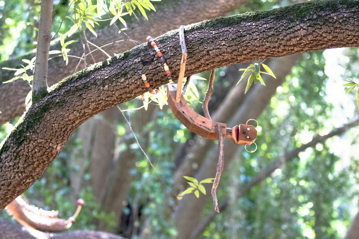 Mokee, one of the trolls along the Bridgeview Trail, hangs from a tree branch on March 31, 2021, in Oakland, Calif.