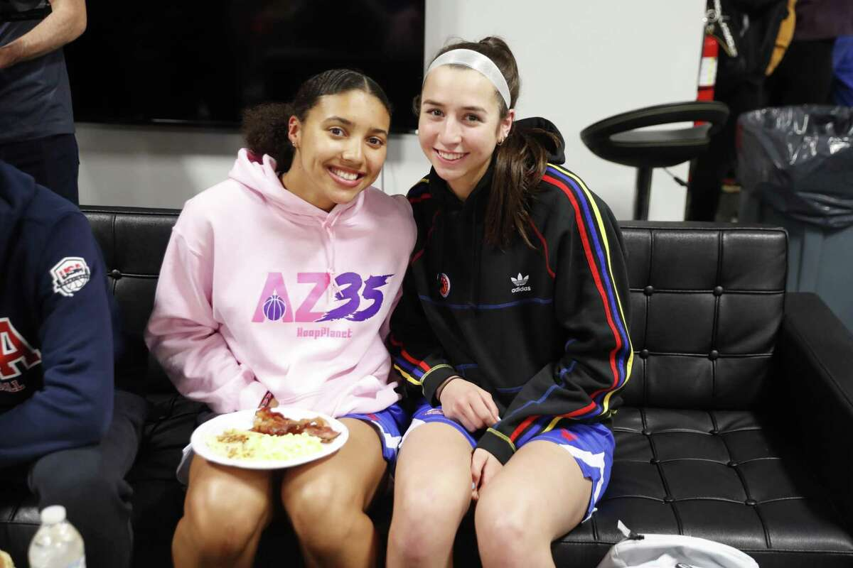 Azzi Fudd, left, and Caroline Ducharme, who both plan to attend UConn, watch a Huskies' game on television during a break at the American Family Insurance High School Slam Dunk & 3-Point Championships at Franklin Central High School in Indianapolis, IN.