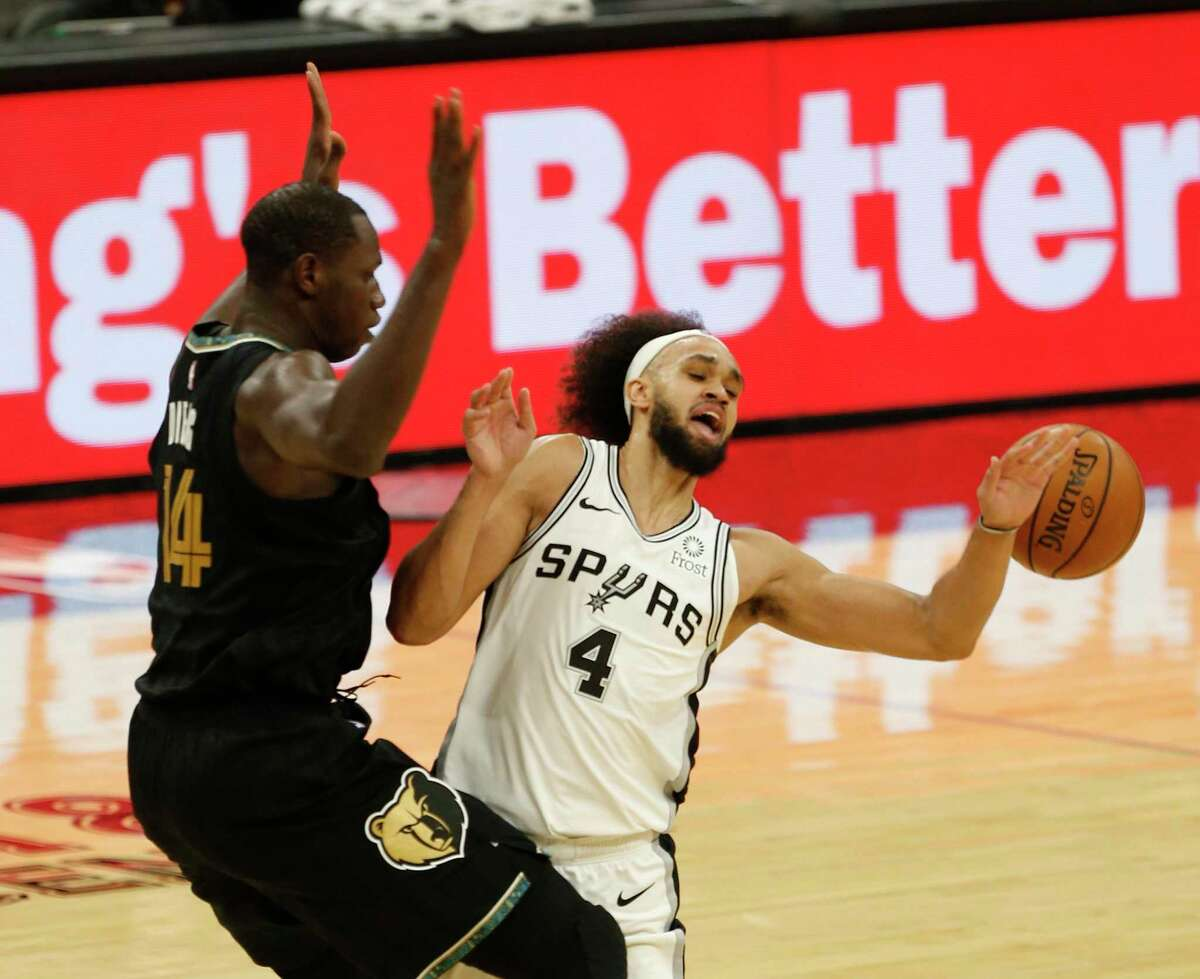 Derrick White #4 of the San Antonio Spurs is fouled by Gorgui Dieng #14 of the Memphis Grizzlies. Grizzlies v Spurs at AT&T Center on Saturday, January 30,2021