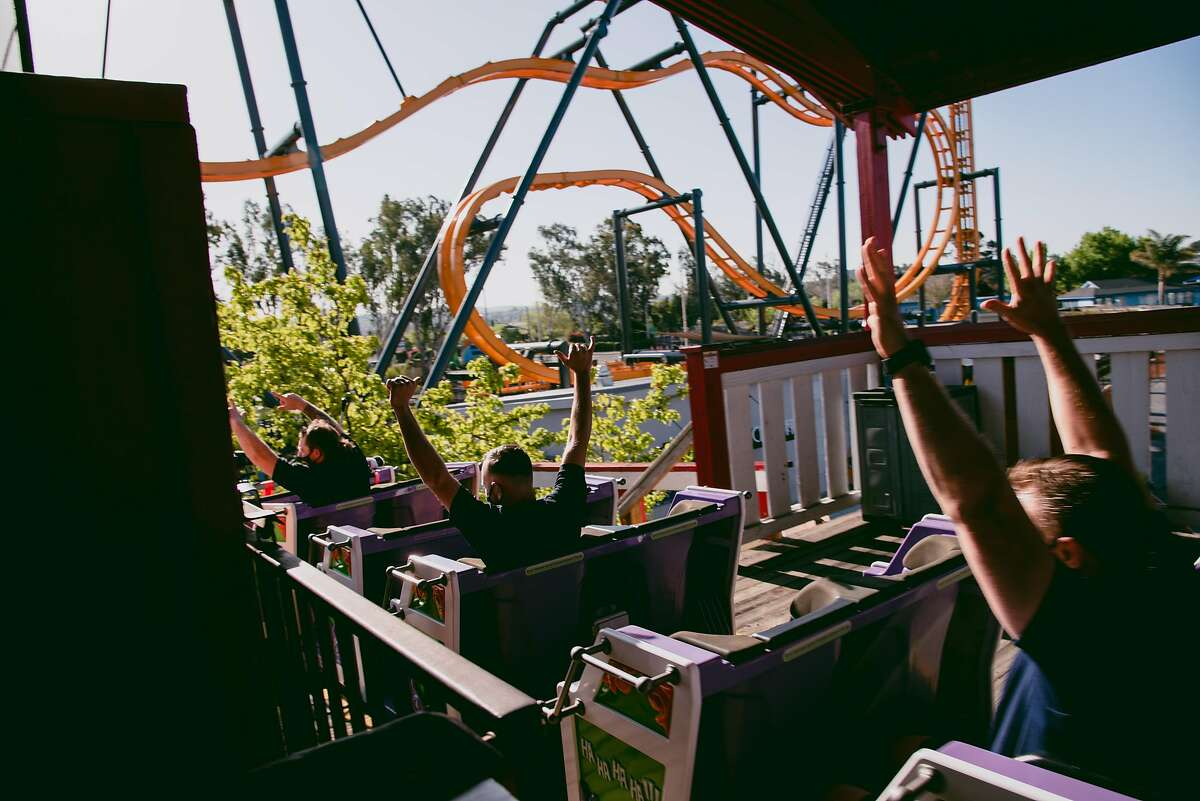 Firefighters ride in a socially distanced roller coaster train at Six Flags Discovery Kingdom in Vallejo.