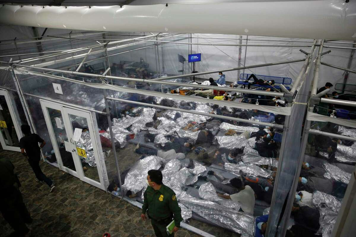 Young children lie inside a pod at the Department of Homeland Security holding facility run by the Customs and Border Patrol on March 30, 2021, in Donna, Texas. The Donna location is the main detention center for unaccompanied children coming across the U.S. border in the Rio Grande Valley. The children are housed by the hundreds in eight pods that are about 3,200 square feet in size. Many of the pods had more than 500 children in them.