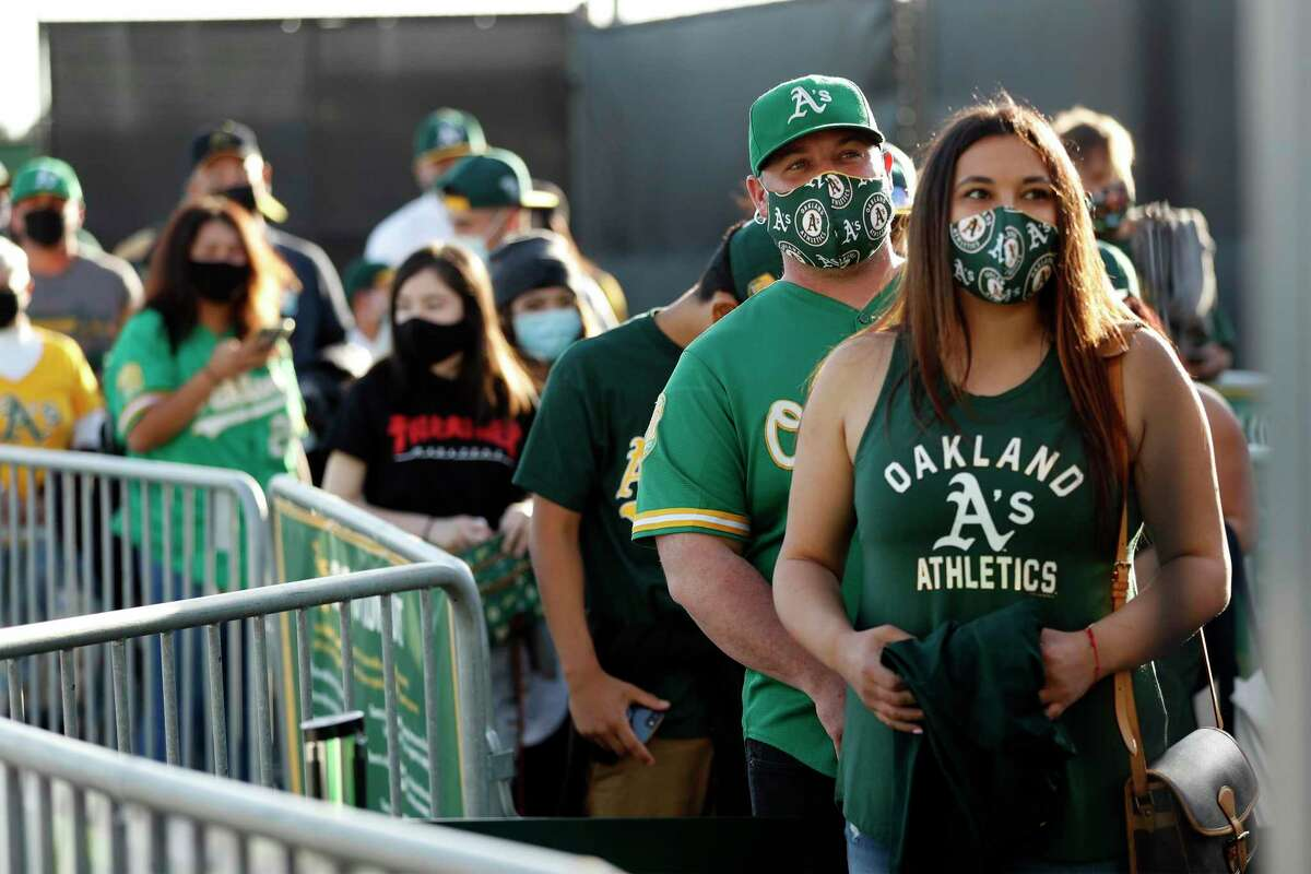 Angela and Nick Tostado of Martinez wait to enter before Oakland Athletics play Houston Astros in season opener at Oakland Coliseum in Oakland, Calif., on Thursday, April 1, 2021.