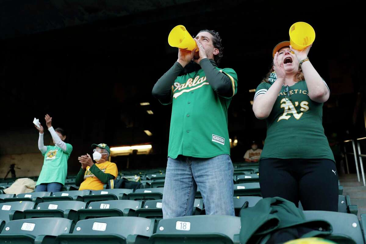 A's fans Mike Manolas and Anne Allen cheer as Oakland Athletics play Houston Astros in season opener at Oakland Coliseum in Oakland, Calif., on Thursday, April 1, 2021.