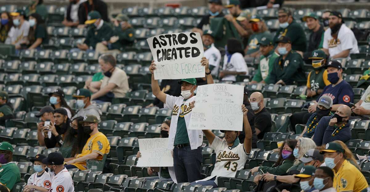 Oakland Athletics fans hold up signs about the Houston Astros cheating during their Opening Day game at RingCentral Coliseum on April 01, 2021 in Oakland, California. (Photo by Ezra Shaw/Getty Images)