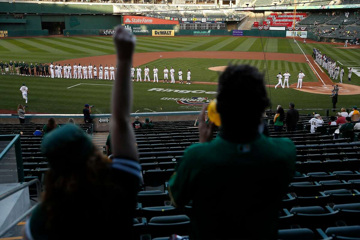A's fans Anne Allen and Mike Manolas cheer as Oakland Athletics' Matt Chapman is introduced before season opener against Houston Astros at Oakland Coliseum in Oakland, Calif., on Thursday, April 1, 2021.