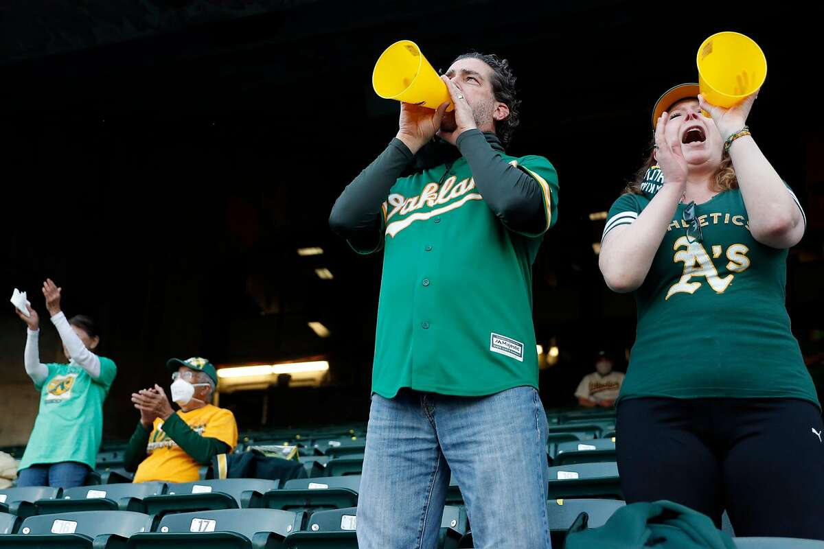 A's fans Mike Manolas and Anne Allen cheer as Oakland Athletics play Houston Astros in the season opener at the Oakland Coliseum.