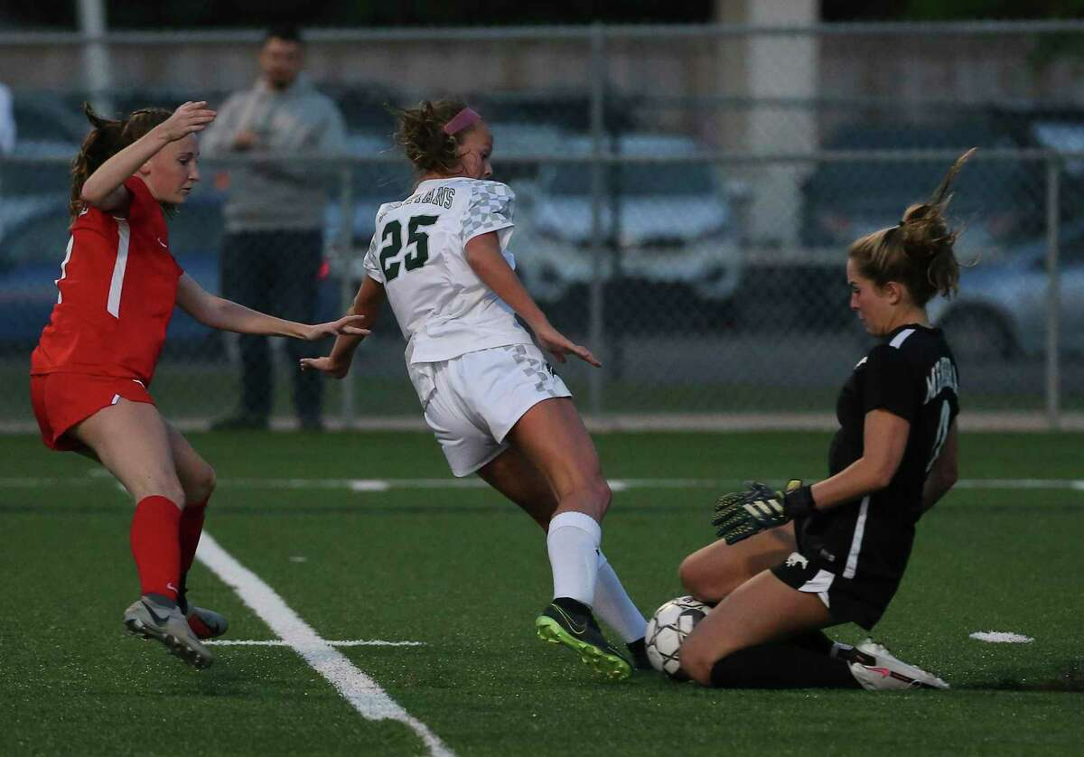 Memorial Mustangs goalkeeper Maddie Dukes comes to take the ball away from Stratford Spartans forward Rileigh Toner during the second half of the conference 6A regional quarterfinal match Thursday, April 1, 2021, at Spring Woods High School in Houston.