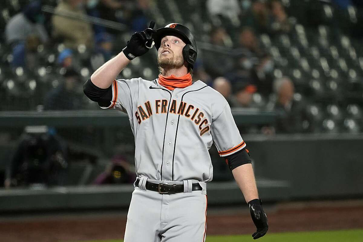 San Francisco Giants' Austin Slater points skyward as he crosses home plate on his solo home run against the Seattle Mariners during the fifth inning of a baseball game Thursday, April 1, 2021, in Seattle. (AP Photo/Elaine Thompson)