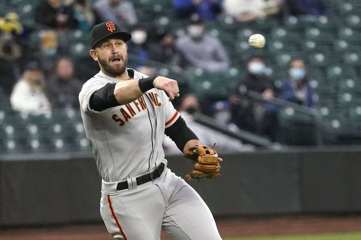 San Francisco Giants third baseman Evan Longoria throws to first for the out after fielding a grounder by Seattle Mariners' Mitch Haniger during the first inning of a baseball game Thursday, April 1, 2021, in Seattle. (AP Photo/Elaine Thompson)