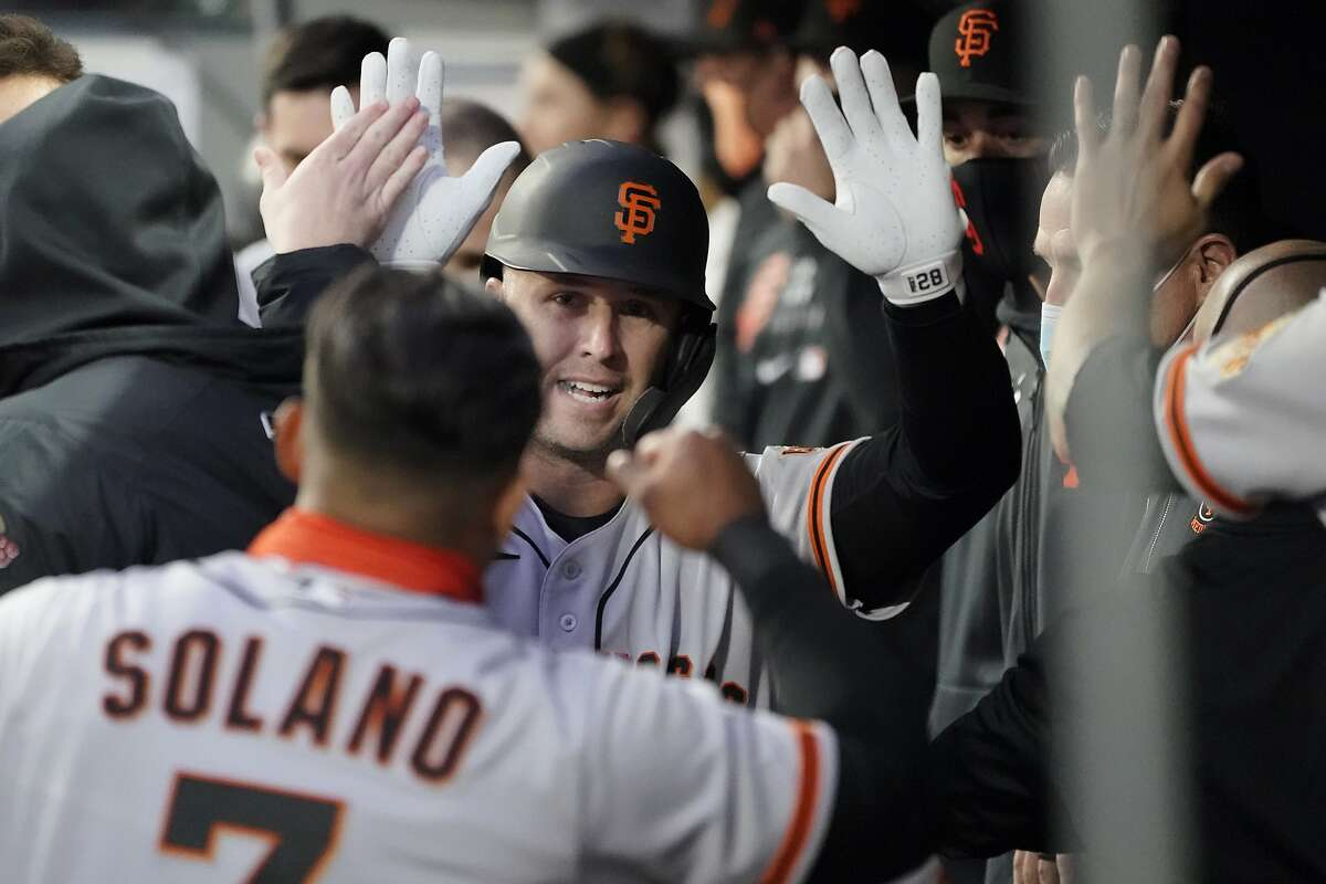 Giants catcher Buster Posey is greeted in the dugout by Donovan Solano after hitting a solo home run in the second inning.