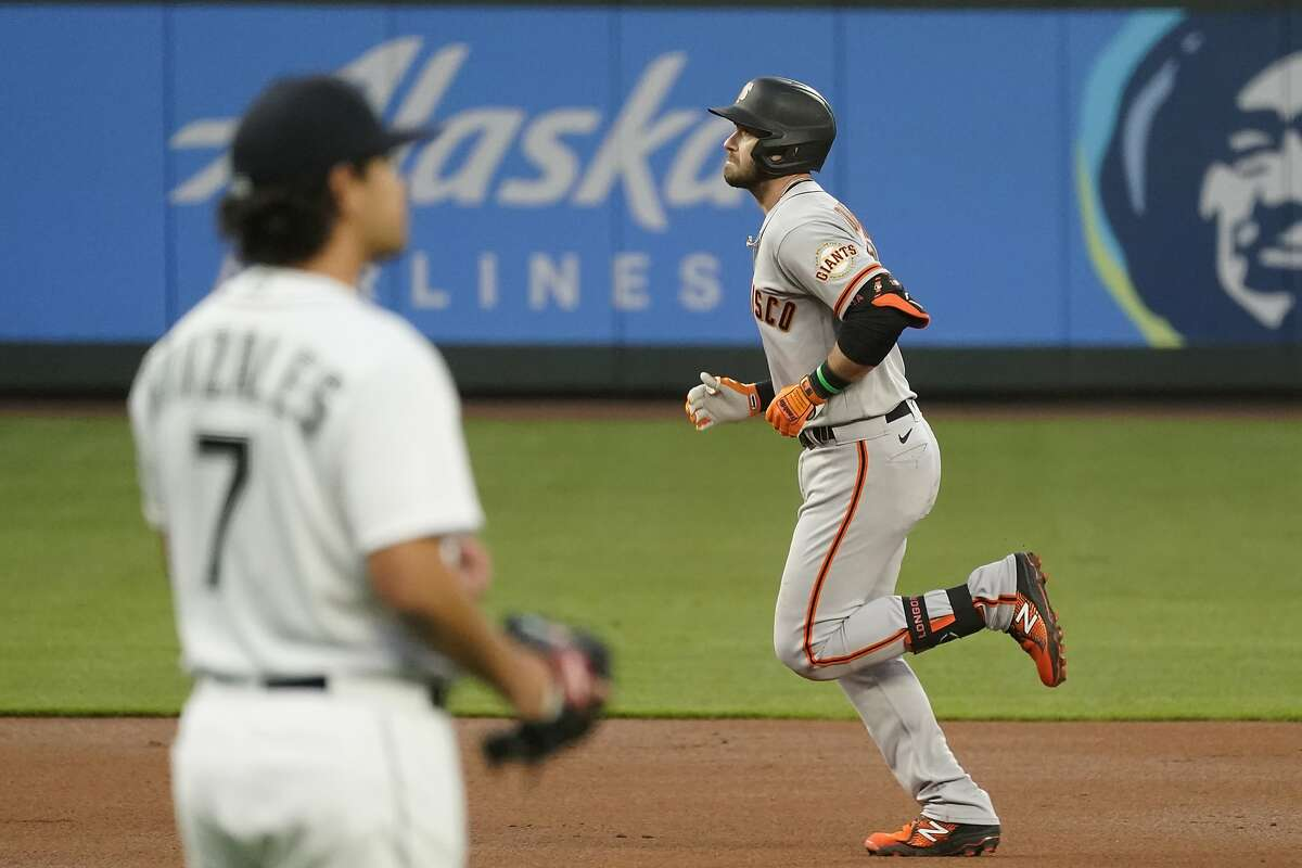 San Francisco Giants' Evan Longoria, right, rounds the bases on a solo home run as Seattle Mariners starting pitcher Marco Gonzales looks toward the outfield during the second inning of a baseball game Thursday, April 1, 2021, in Seattle. (AP Photo/Elaine Thompson)