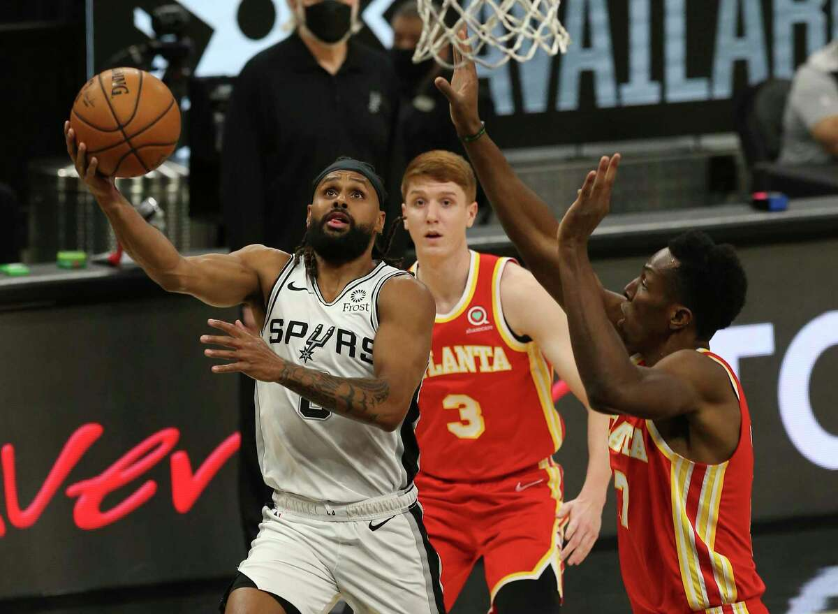 Spurs' Patty Mills (08) attempts a layup against Atlanta Hawks' Onyeka Okongwu (17) during their game at the AT&T Center on Thursday, Apr. 1, 2021.