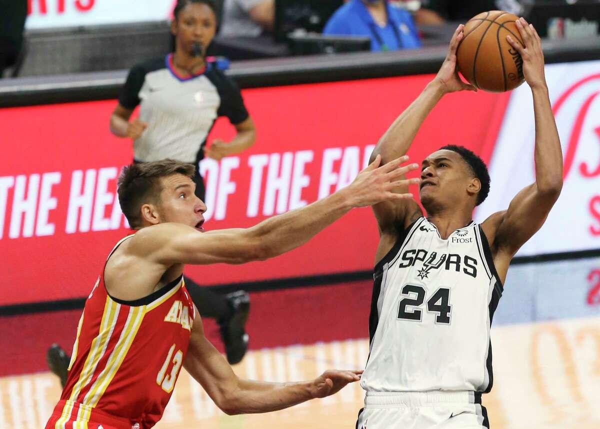Spurs' Devin Vassell (24) scores against Atlanta Hawks' Bogdan Bogdanovic (13) during their game at the AT&T Center on Thursday, Apr. 1, 2021.