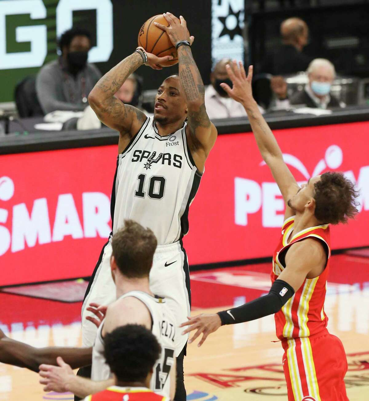 Spurs' DeMar DeRozan (10) shoots against Atlanta Hawks' Trae Young (11) during their game at the AT&T Center on Thursday, Apr. 1, 2021.