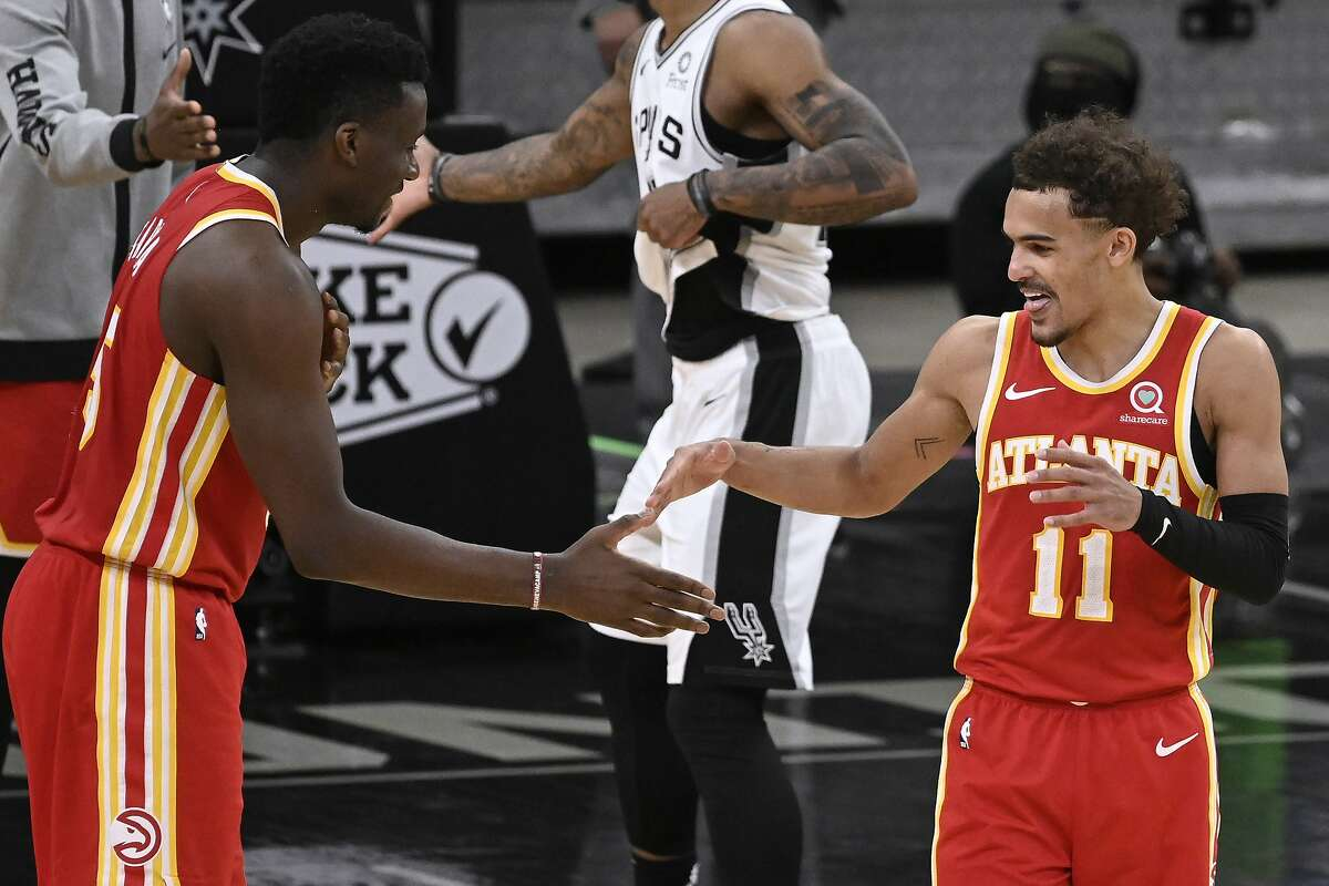 Atlanta Hawks' Trae Young (11) and Clint Capela celebrate the team's double-overtime victory against the San Antonio Spurs in an NBA basketball game Thursday, April 1, 2021, in San Antonio. Atlanta won 134-129. (AP Photo/Darren Abate)