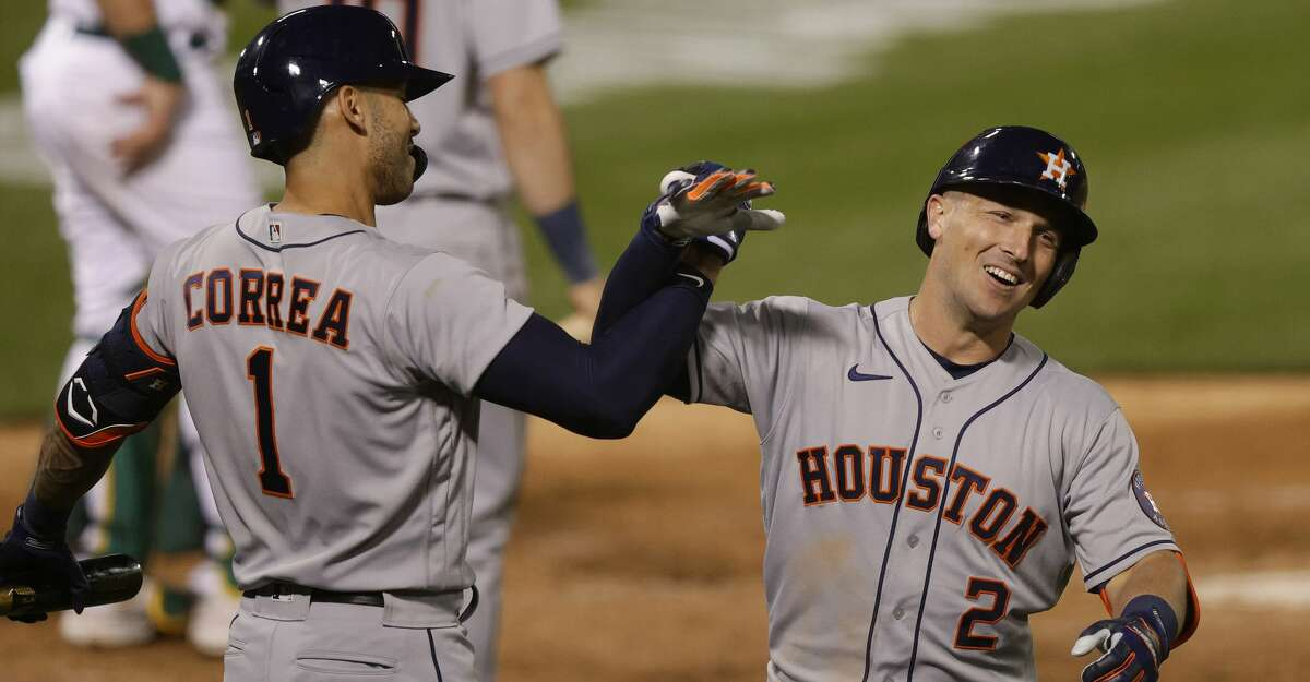Alex Bregman #2 of the Houston Astros is congratulated by Carlos Correa #1 after he hit a home run in the eighth inning against the Oakland Athletics during their Opening Day game at RingCentral Coliseum on April 01, 2021 in Oakland, California. (Photo by Ezra Shaw/Getty Images)