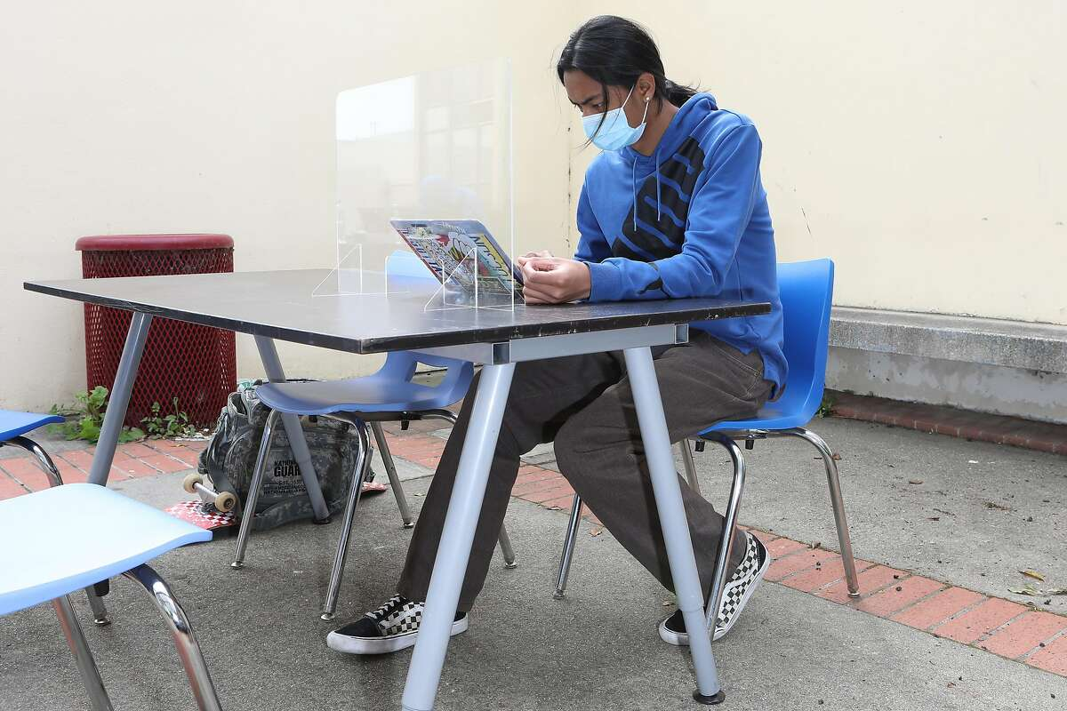 Andrew Taate, a freshman, works at a desk in a courtyard at Thurgood Marshall High School in San Francisco. Teachers meet with students outside the school on Wednesdays to provide them with a range of support.