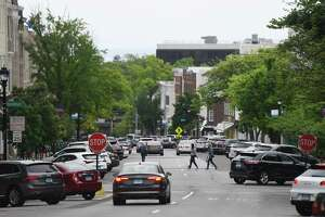 Pedestrians cross the Greenwich Avenue at its intersection with Arch Street last year in Greenwich.
