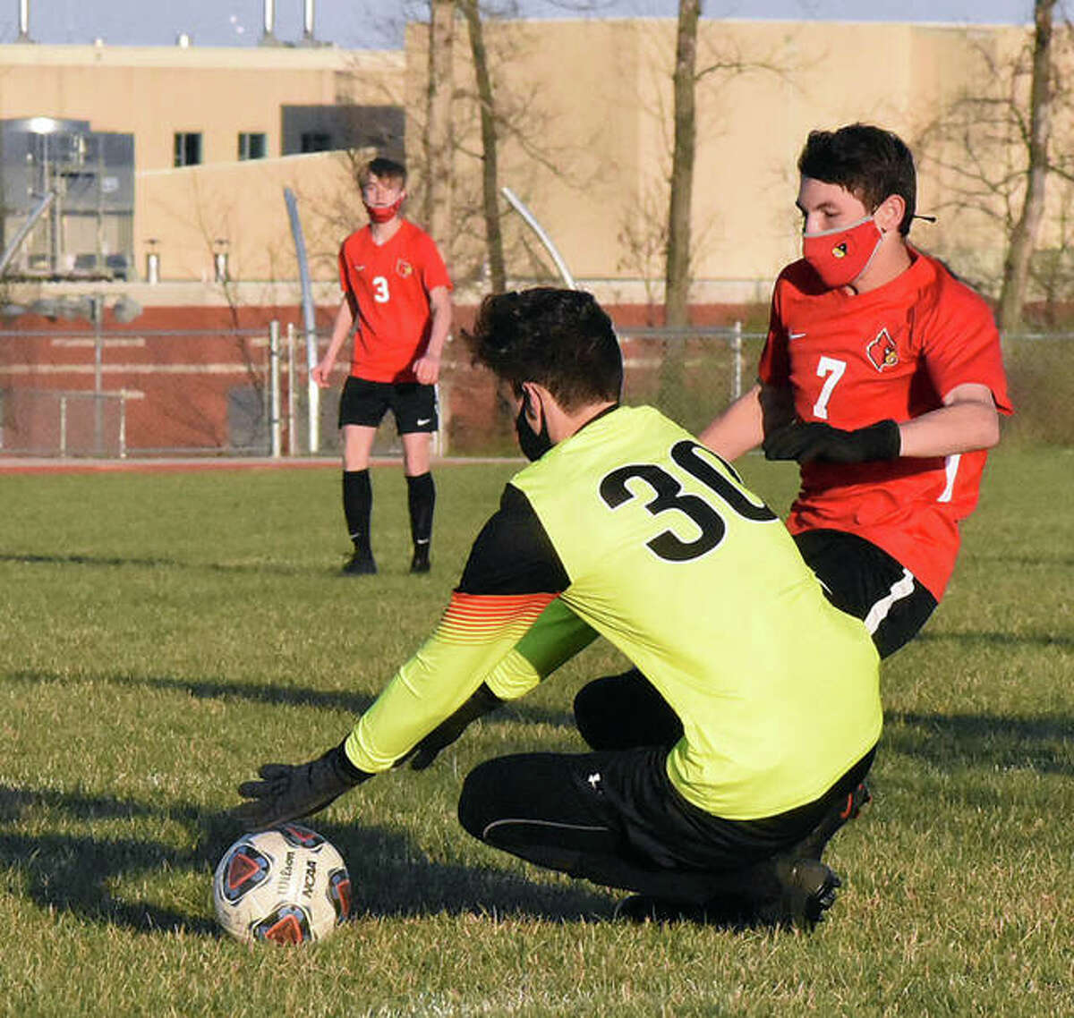 EHS keeper Kadin Chiapelli covers up a ball in the 18-yard box before Alton's Nick Rayfield can get a foot on it early in Thursday's game.