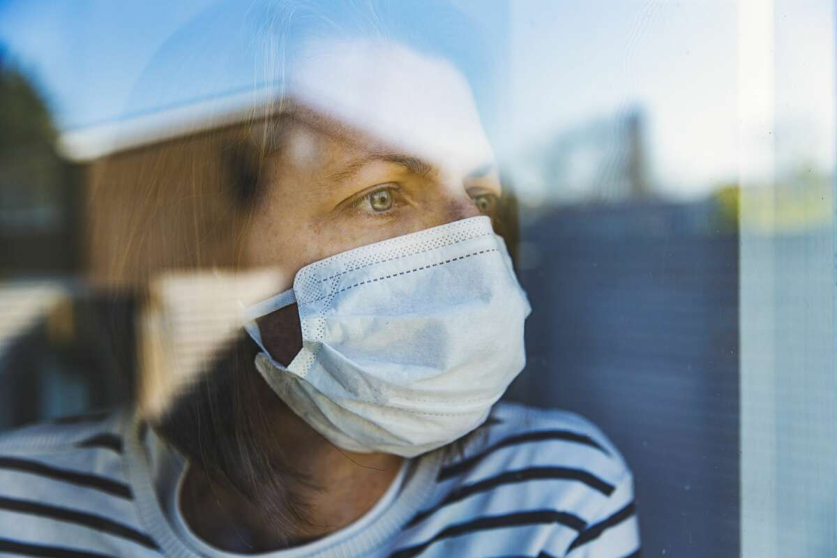 Woman in a mask looking through a window - stock photo