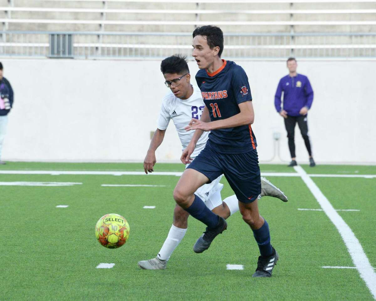 Luciano Torres (11) of Seven Lakes dribbles past Jonahan Lopez (23) of Jersey Village during the second half of Region III Area Round soccer playoff match between the Seven Lakes Spartans and the Jersey Village Falcons on Tuesday, April 2, 2019 at Legacy Stadium, Katy, TX.